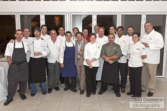 In front row from left to right are: Rizwan Ahmed of Hourglass Brasserie, Ryan Escudé of Centro, Chris Kattawar of D. Carlo Trattoria, Matthew Varga of Gracie's, Kevin Gaudreau of The Pier, Melissa Denmark of Gracie's, David Blessing of Belle Mer and Jennifer Chapman of DeWolf Tavern. In back row from left to right are:  Michael Conetta of Trio, Raymond Montaquilla of the Coast Guard House, Eric Haugen of Ocean House, Rick Allaire, David Cardell of Temple, Andrew Shotts of Garrison Confections, Karsten Hart of Castle Hill Inn, Ben Lacy of Tastings Wine Bar & Bistro, Sai Viswanath of DeWolf Tavern, Christian Pieper of Salvation Café and Brian Kingsford of Bacaro. Missing from the photo are the following chefs: Jules Ramos of 1149, Kevin Thiele of One Bellevue, Kim Lambrechts of Grill at 41 North, Jonathan Cambra of the Boat House, and Antonio Franco of Pane e Vino