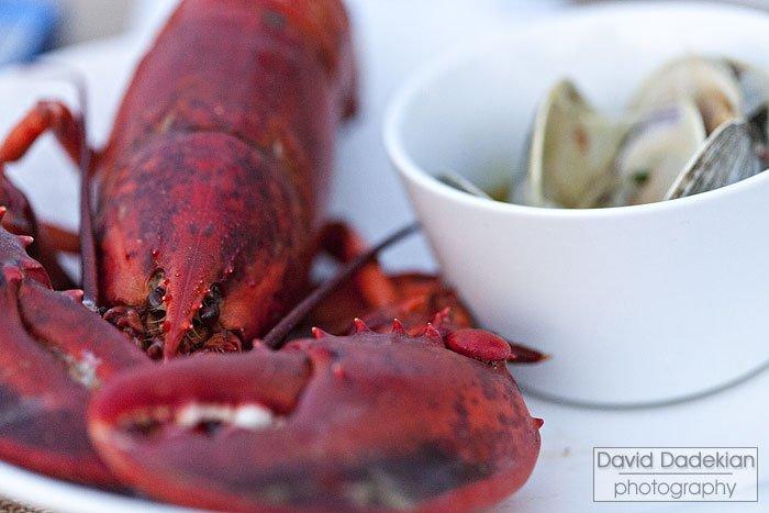 Lobster alongside steamed Littlenecks with smoked seaweed-vihno verde broth